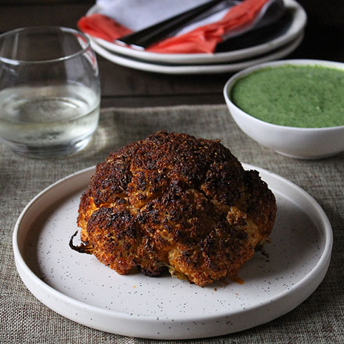 Spiced Whole Roasted Cauliflower with Green Herb Yogurt Sauce